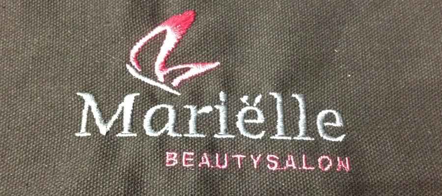 Multi kleur geborduurde borst logo's op kappers cape door van Veldhuizen Reclame.